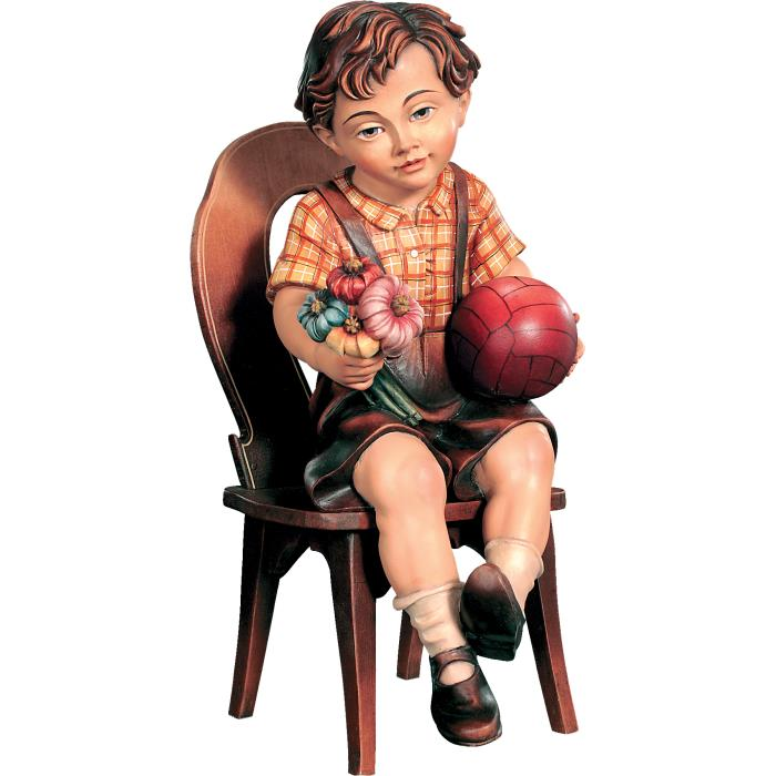 Sitting boy with ball on chair